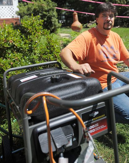 Randy Race of Parkville kneels next to the $800 generator he purchased Sunday. He has been without power since Friday's storms.