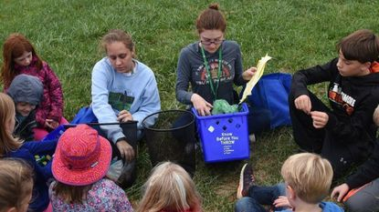 Environmental educator Becky Schoppet, left, and Elena Wichers, right, an environmental educator intern, teach children about recycling at Howard County Conservancy.