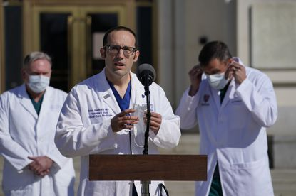 Dr. Brian Garibaldi talks with reporters Monday at Walter Reed National Military Medical Center in Bethesda.
