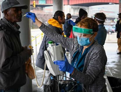 Nurse Molly Greenberg takes Asrat Alemayhu's temperature before he can enter Health Care for the Homeless in downtown Baltimore last month. All clients were being screened because of the current coronavirus outbreak.