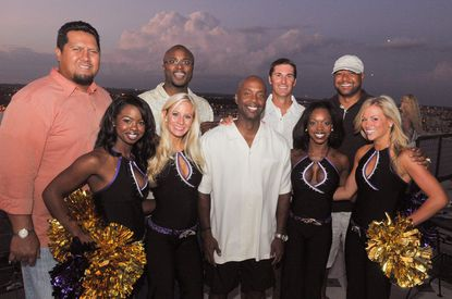 Sean Hull (center) is surrounded by Ravens (from left) Ed Mulitalo, Qadry Ismail, Matt Stover and Brad Jackson) and four cheerleaders, whose names were unavailable.