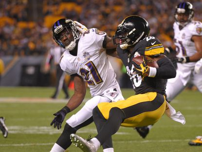Ravens' Lardarius Webb stops Steelers' Le'veon Bell during the first quarter of the Ravens game against the Steelers at Heinz Field in Pittsburgh.