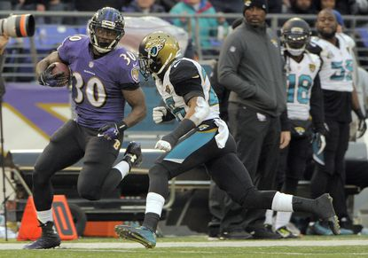 Ravens running back Bernard Pierce (30) gains 27 yards as he is pursued by Jacksonville Jaguars safety Josh Evans during the fourth quarter Sunday, Dec. 14, 2014. Baltimore held on to win, 20-12.