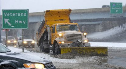A snowplow moves a wave of ice, snow and water as it clears the roads on Jan. 21 on Crain Highway in Glen Burnie.