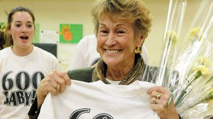 """North Harford girls varsity basketball head coach Lin James displays her """"600 Baby !!"""" T-shirt made in honor of her 600th win in 2012 at North Harford."""