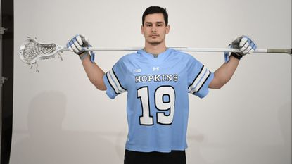 Johns Hopkins senior long-stick midfielder Robert Kuhn poses in the No. 19 jersey he will wear for the 2019 season. The number had belonged to defenseman Jeremy Huber, who died Jan. 26, 2015. Bob and Nancy Huber gave their approval for Kuhn to wear their late son's number.