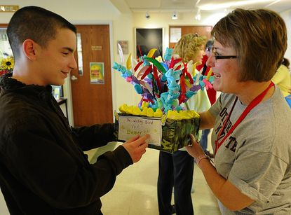 Bob Nobles, 16, of New Windsor, turns in his PEEP artwork to Sandy Oxx, director of the Carroll County Art Council on Monday for the Council's Spring fund raiser.