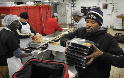 Joshua Anderson loads hot meals, prepared at the Meals on Wheels of Central Maryland, into portable heated bags that will be delivered to local residents. Volunteers deliver food and check on the homebound to make sure they aren't cold or in danger.