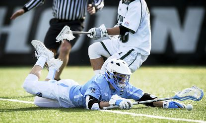 Johns Hopkins attacker Ryan Brown (4) cannot stop himself as he slides past a loose ball as Loyola defender Foster Huggins (20) tracks him late in the fourth quarter at Ridley Athletic Complex on Feb. 20, 2016.