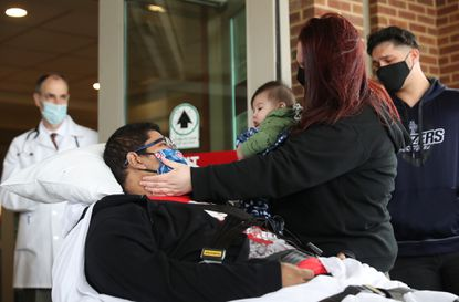 Jonathan Davila is greeted by his wife, Ashley King, with their 6-month-old son, Elijah, after being discharged from Elmhurst Hospital Tuesday, May 5, 2020, in Elmhurst, Ill. in suburban Chicago. Davila, 30, was among the first COVID-19, or coronavirus, patients at the hospital and spent 44 days inside, including 20-plus days intubated for respiratory failure. (John J. Kim/Chicago Tribune)