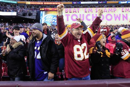Washington Redskins fans cheer next to a Baltimore Ravens fan after the Redskins tied the game in the fourth quarter of the Redskins 31-28 overtime win at FedExField.