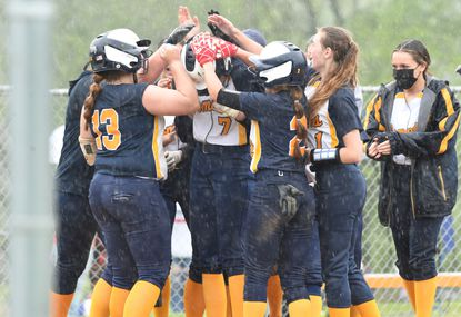 Catonsville teammates surround Maggie Kries (7) as she touches home to celebrate her 2-run home run against Sparrows Point during a softball game at Catonsville High School on Friday, May 7, 2021.