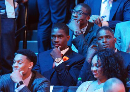 C.J. Fair, middle, waits in the stands after the conclusion of the first round of Thursday night's NBA draft.