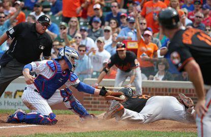 Cubs catcher John Baker tags Chris Davis for the inning-ending out.