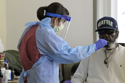 """In this April 17, 2020, photo, Dr. Gabrielle Beger, left, takes a nose-swab sample from Lawrence McGee, right, as she works with a team of University of Washington medical providers conducting testing for the new coronavirus at Queen Anne Healthcare, a skilled nursing and rehabilitation facility in Seattle. More than 100 residents were tested during the visit, and the results for all were negative, according to officials. Sending """"drop teams"""" from University of Washington Medicine to conduct universal testing at skilled nursing facilities in collaboration with public health officials is one aspect of the region's approach to controlling the spread of the coronavirus. (AP Photo/Ted S. Warren)"""