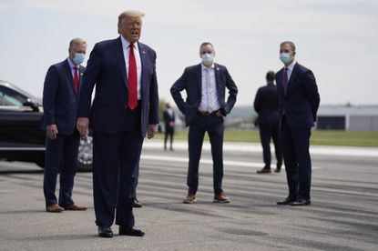 In this May 14, 2020 file photo, President Donald Trump speaks after exiting Air Force One at Lehigh Valley International Airport in Allentown, Pa. From the U.S. president to the British prime minister's top aide and far beyond, leading officials around the world are refusing to wear masks or breaking confinement rules meant to protect their populations from the coronavirus and slow the pandemic. While some are punished when they're caught, or publicly repent, others shrug off the violations as if the rules don't apply to them. (AP Photo/Evan Vucci, File)
