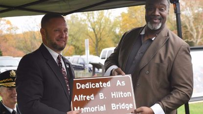 Kevin Reigurt, left, Executive Director, Maryland Transportation Authority presents Mr. Peter Byrd, a decendent of Alfred B. Hilton, with a replica sign for the Alfred B. Hilton Memorial Bridge during Thursday's dedication ceremony at the Alfred B. Hilton Park.