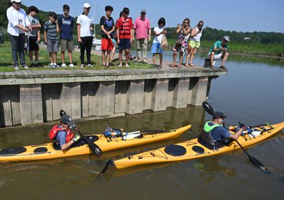 Hearly Mayr, right, and his son Andreas climb into their kayaks with friends and family cheering them on from the bulkhead as they set off from the Elk River boat launch in Elkton Friday July 16, 2021 for their 12-day, 200 mile adventure down the Chesapeake Bay. The Bay 200 Challenge is supporting the Adventist Development and Relief Agency's (ADRA) COVID-19 hunger pandemic response campaign, which aims to raise US$3 million by July 31.