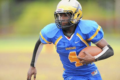 Laurel's Oluwaseyi Sodipo carries the ball up the field during the Spartans' 21-13 loss to Suitland on Oct 3.