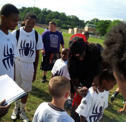 Ravens cornerback Lardarius Webb, center, signs autographs during his football camp at Towson University.