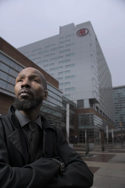 Jazz Baxter, who worked as a banquet server stands outside the Hilton Hotel Baltimore, who chose to lay off him and other workers as the coronavirus pandemic decimates the hotel industry Tue., Jan. 26, 2021. Many are struggling with long-term unemployment after building steady careers in the sector. (Karl Merton Ferron/Baltimore Sun Staff)
