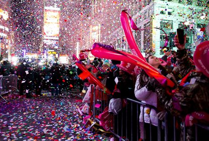 Revelers are engulfed by confetti in Times Square just after midnight during New Year's Eve festivities in New York, Thursday, Jan. 1, 2015.