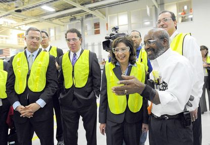 From left, Gov. Martin O'Malley, Baltimore County Executive Kevin Kamenetz and U.S. Labor Secretary Hilda Solis gets a tour of the heavy-duty assembly line from Johnnie Nelson, a union auto worker at the General Motors' White Marsh plant.