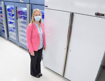 Lisa Polinsky, assistant vice president of pharmacy services for LifeBridge Health, poses Nov. 11, 2020, for a photo in front of the refrigerators, left, and the freezer, right, they normally use for vaccines at Sinai Hospital in Baltimore. The hospital bought even colder freezers to store COVID-19 vaccines.