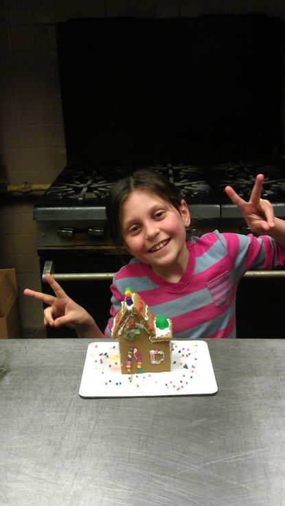 Bella Coleman, then 9, shows off her gingerbread house during last year's Christmas party at Roosevelt Recreation Center in Hampden.
