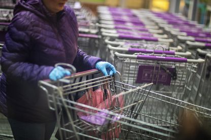 A shopper wears gloves upon entering a Stop & Shop supermarket during hours open daily only for seniors Thursday, March 19, 2020, in North Providence, R.I. Should store clerks be required to wear them, too?