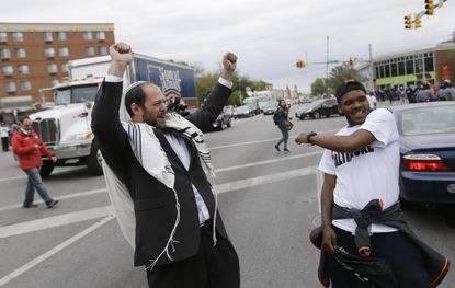 """Rabbi Yerachmiel Shapiro, left, and Robert """"Meech"""" Tucker celebrate in an iconic photo after six Baltimore police officers were charged in connection with death of Freddie Gray. Tucker died last month at the age of 29."""