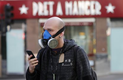 A man wears a mask as he walks through London. Britain's Prime Minister Boris Johnson has imposed its most draconian peacetime restrictions due to the spread of the coronavirus on businesses and social gatherings. Too bad American conservatives won't support this idea.