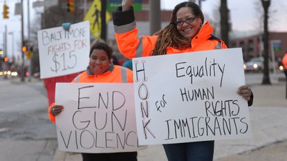 "Patrice Meekins, 41, left, and Jackie Edwards, 54, right, volunteers or ""hug dealers"" with ""Hugs Don't Shoot,"" hold signs in front of the State Center. They were part of a demonstration held Thursday in honor of International Women's Day, organized by Baltimore Women United."