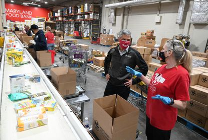 Maryland Food Bank President & CEO Carmen Del Guercio chats with regular volunteer Denise Phillips of Catonsville, right, at the facility in Baltimore on Thursday, March 25, 2021.