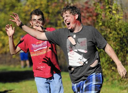 McDaniel Students Tyler Junkin-Mills, right, and Andy Strakna reach towards runners as zombies during the 5k Zombie Run in Westminster Saturday, Oct. 18, 2014.