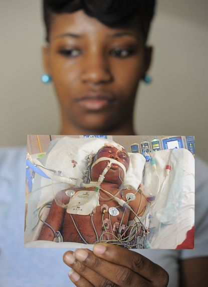 Cordedra Scott holds a picture of her brother, Jerrod Pridget that she took when he was in the hospital after being beaten. A recent string of homicides in state prisons has left families rattled and angry about the conditions that led to their loved ones' deaths, but state officials say they have made large improvements in prison safety in recent years.