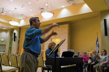 Marshall Kohen leads three choirs from 10 Laurel churches in rehearsal for the upcoming Interfaith Thanksgiving music service at Temple Isaiah in Fulton which will be held on Nov. 22, on Wednesday, November 9th.