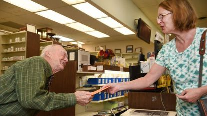 Becky Dorothy, right, hands her friend Eugene Streett, owner of Boyd & Fulford Drugs Store, a birthday card during her visit to the Main Street store Friday afternoon. Streett celebrated his 89th birthday Friday spending the majority of his day behind the counter.