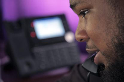 Elijah McBride, a counselor at Baltimore Crisis Response Inc. that runs the Here2Help hotline, speaks on the phone at his workstation to a spouse whose manic partner refuses to accept help on Sept. 9, 2020. (Karl Merton Ferron/Baltimore Sun Staff)