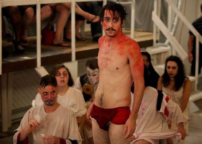"Trevor Wilhelms as Marat and ensemble in Annex Theater's production of ""Marat/Sade"""