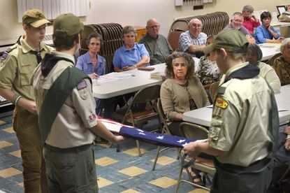 Members of Taneytown Boy Scout Troop 718 fold the Star Spangled Banner at the meeting of the Taneytown Heritage Committee on Monday before presenting the flag to the owners of Tera Rubra.