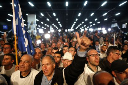 Supporters of Benjamin Netanyahu cheer as they hear the first television predictions of results after polls closed, in Tel Aviv, Israel, on Tuesday, March 17.
