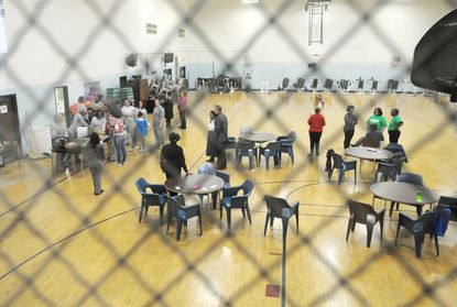 Prison officials, inmates, children and guests occupy the gym for the troop meeting. Since 1992 a program called Girl Scouts Beyond Bars at the Maryland Correctional Institute for Women in Jessup has been host to Girl Scout Troops for girls to spend bonding time with their inmate mothers.