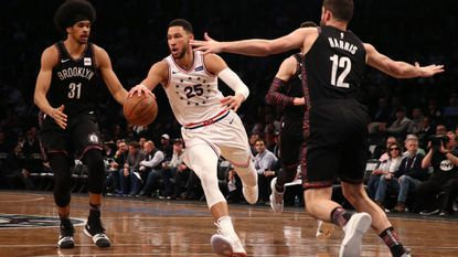 Philadelphia 76ers' Ben Simmons (25) of the Philadelphia 76ers handles the ball against Brooklyn Nets' Jarrett Allen (31) and Joe Harris (12) in the third quarter during Game 3 of round one of the NBA playoffs on Thursday.