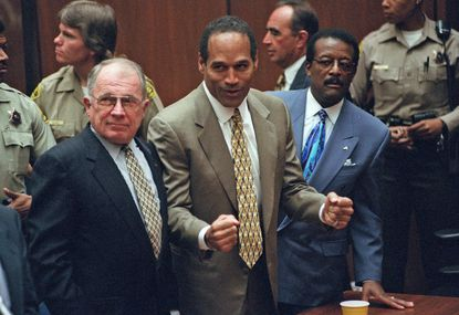 O.J. Simpson reacts in 1995 as he is found not guilty of murdering his ex-wife, Nicole Brown Simpson, and her friend Ronald Goldman. With him are members of his defense team, F. Lee Bailey, left, and Johnnie Cochran Jr.