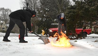 From left, Justin Cheetham, owner of Remarkable Home, and Ricky Claudio, foreman, melt ice on a sidewalk in Guilford with a roofing torch and gasoline. Cheetham says by melting the top layer of ice then applying salt, they can melt the thick ice without hurting the concrete.