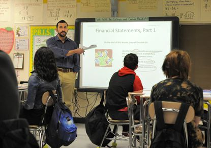 Baltimore,MD -- 2/6/15 -- Jesse Chacona is a math teacher at Hampden Elementary/Middle School where he teaches the Stocks in the Future program to a group of eighth graders. Stocks in the Future, which is a financial literacy program designed for middle school youth.