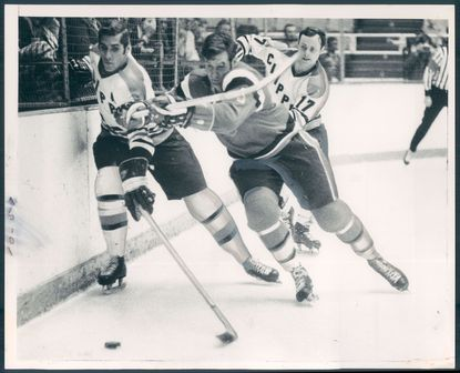 Marc Dufour of the Clippers (left) and Ray Clearwater of Providence dig for puck in Calder Cup playoff game won by Baltimore, 4-2, at the Civic Center on April 16, 1971. The Clippers' John Cunniff trails the play.