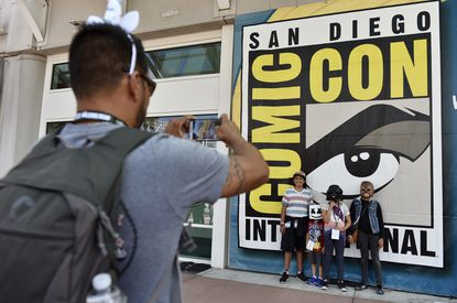 Luis Ramos, left, of San Diego takes a picture of his son Alek, 6, third from right, and daughter Anabel, 11, second from right, and their friends Emiliano Beltran, 12, fourth from right, and Isabel Beltran, 10, before Preview Night at the 2018 Comic-Con International at July 18, 2018, in San Diego.