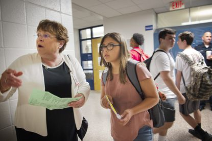 In Bristol, Conn., Bristol superintendent Sue Moreau, at left, helps to direct freshman Haley Wells, 14, to a classroom at Bristol Eastern High School on Thursday morning on the first day of school.